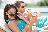 Couple with drinks by swimming pool