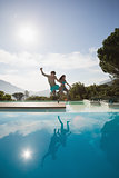 Cheerful couple jumping into swimming pool