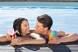 Cheerful couple with drinks in swimming pool