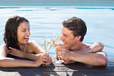 Cheerful couple toasting champagne in swimming pool