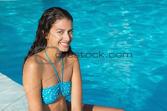 Beautiful young woman by swimming pool