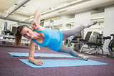 Fit brunette doing pilates on exercise mat