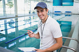 Handsome swimming instructor smiling at camera