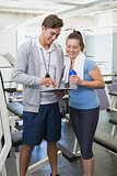 Personal trainer and client looking at clipboard together