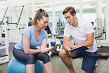 Personal trainer working with client holding dumbbell
