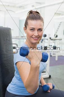 Fit brunette lifting blue dumbbells