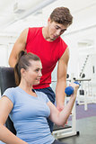 Personal trainer helping client lift dumbbell