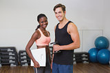 Personal trainer working with client holding scales