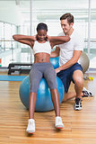 Personal trainer working with client on exercise ball