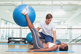 Personal trainer working with client holding exercise ball