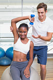 Personal trainer helping client lift dumbbell on exercise ball