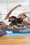 Fit couple warming up on exercise mats