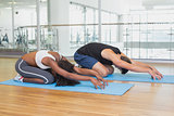 Fit couple in childs pose on exercise mats