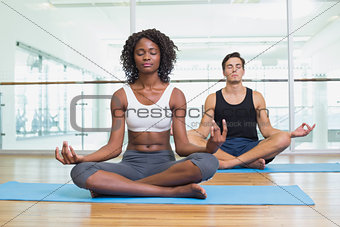 Fit couple sitting in lotus pose in fitness studio