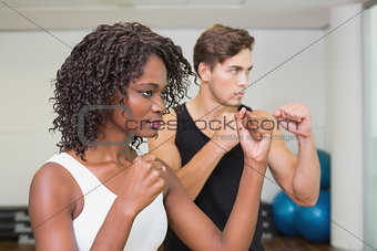 Fit couple standing with fists raised