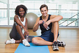 Personal trainer and client smiling at camera on exercise mat