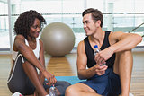 Personal trainer and client smiling at each other on exercise mat