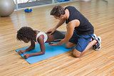 Personal trainer working with client on exercise mat