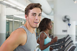 Fit man smiling at camera on treadmill