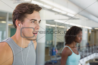 Fit man running on treadmill listening to music