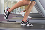 Fit man and woman running on treadmill