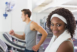Fit woman smiling at camera on treadmill