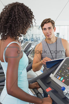 Fit woman on treadmill talking to personal trainer