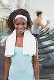 Pretty woman smiling at camera beside treadmills