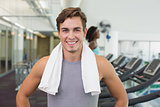 Handsome man smiling at camera beside treadmills
