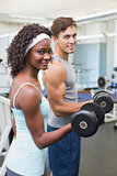 Fit couple lifting dumbbells together
