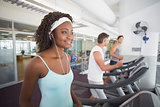 Fit woman on treadmill listening to music