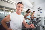 Fit man running on treadmill smiling at camera