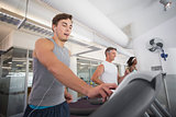 Fit man running on treadmill listening to music