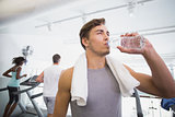 Fit man drinking water beside treadmills