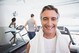 Fit man smiling at camera beside treadmills