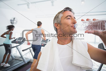 Fit man drinking water beside treadmills