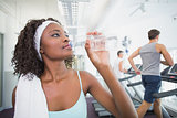 Fit woman drinking water beside treadmills