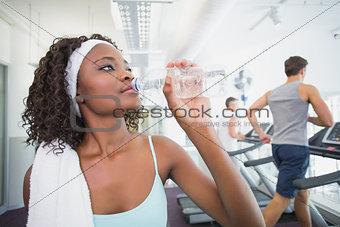 Fit woman drinking water beside treadmills