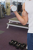 Fit man holding heavy dumbbell
