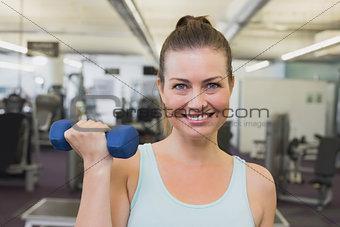 Fit brunette holding blue dumbbells