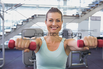 Fit brunette holding red dumbbells