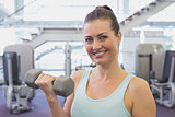 Fit brunette holding grey dumbbell
