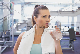 Fit brunette drinking water with towel around shoulders