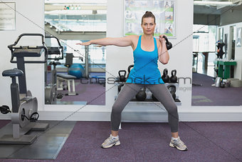 Fit brunette working out with kettlebell