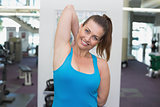 Fit brunette warming up in fitness studio