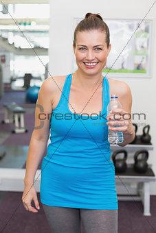 Fit brunette smiling at camera in fitness studio