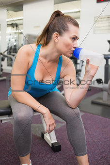 Fit brunette drinking from sports bottle
