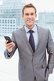 Businessman holding mobile phone in office
