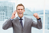 Cheerful businessman using mobile phone