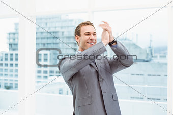 Businessman clapping hands in office